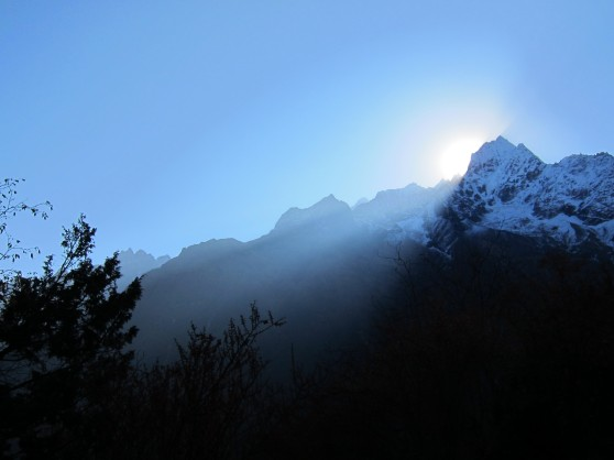 Sun shining behind the mountain at the start of our trek